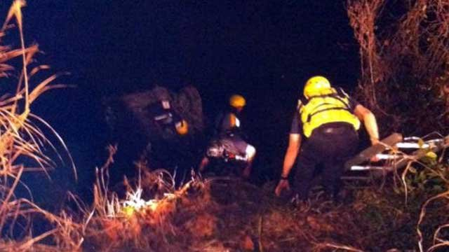 Rescuers work to free a driver from a car that was nearly submerged in water after a crash. (Dec. 2, 2012/Asheville Fire Dept.)
