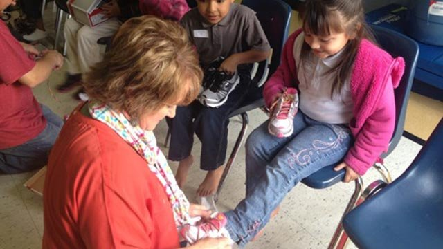NewSpring Church members put shoes on students at Grove Elementary. (Dec. 5, 2012/FOX Carolina)