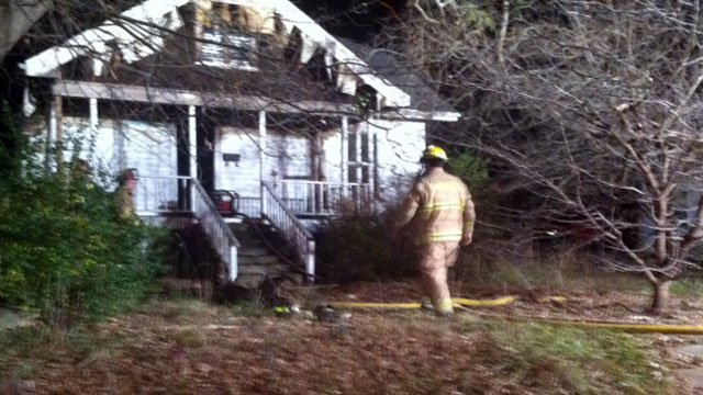 Firefighters mill about the scene of a fire at a vacant Spartanburg home. (Dec. 6, 2012/FOX Carolina)