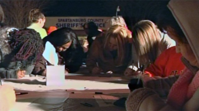 Some sign cards to send to Newtown, CT, to show support at the vigil in Spartanburg on Tuesday. (Dec. 18, 2012/FOX Carolina)