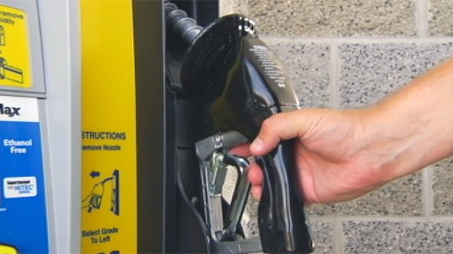 A driver picks up the handle of a gas pump at a Greenville station. (File/FOX Carolina)