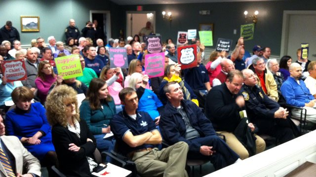 Nearly a dozen people hold up signs of support for former Simpsonville police chief Keith Grounsell during a council meeting. (Jan. 8, 2013/FOX Carolina)