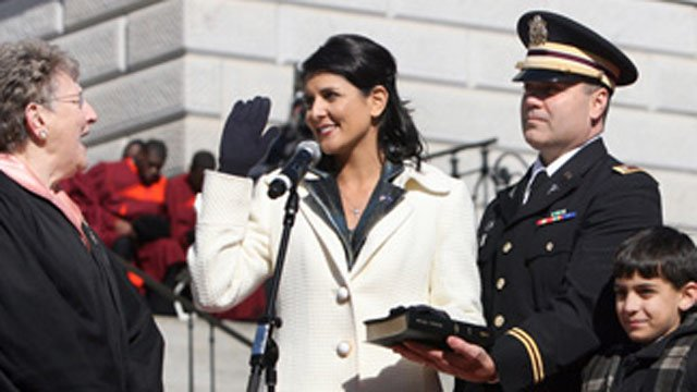 Michael Haley (right) holds the Bible for his wife, Gov. Nikki Haley, during her inauguration. (File/FOX Carolina)