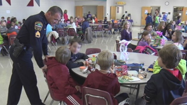 An off-duty deputy talks with Anderson Mill Elementary School students in the cafeteria while on patrol. (Jan. 7, 2013/FOX Carolina)