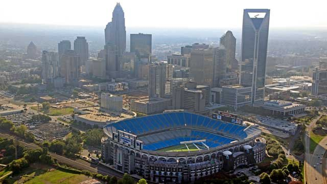 In this Aug. 16, 2012 file photo, the skyline of Charlotte, N.C., rises behind Bank of America Stadium. (AP Photo/Chuck Burton, File)