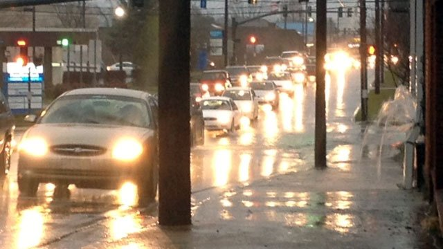 Cars drive through water standing on a street in Hendersonville during rush hour. (Jan. 30, 2013/FOX Carolina)