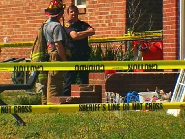 Investigators look over the scene of a Taylors fire where two people were found dead. (April 3, 2011/FOX Carolina)