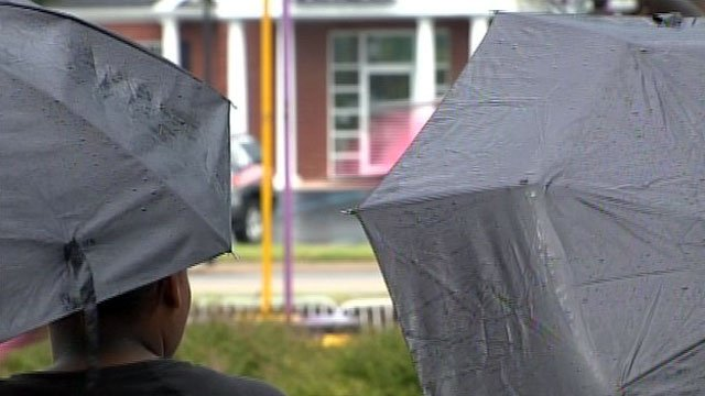 Two people hold umbrellas outside an elementary school. (File/FOX Carolina)