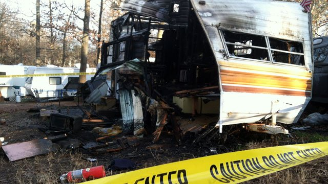 Caution tape surrounds the charred remains of a camper in Greer after an explosion. (Feb. 14, 2013/FOX Carolina)