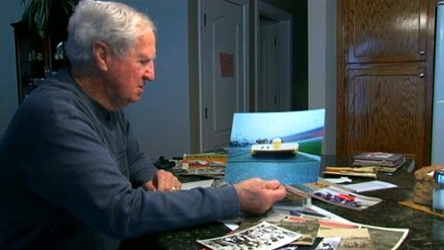 Junior Neal holds a photo of the race car he drove when he won in Daytona. (File/FOX Carolina)