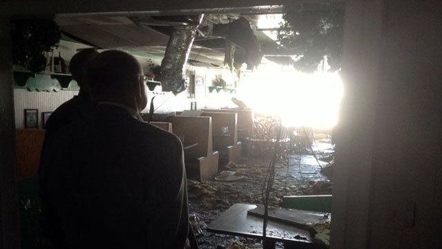 Two people look over the damage left behind by a fire at a Piedmont restaurant. (March 6, 2013/FOX Carolina iWitness)