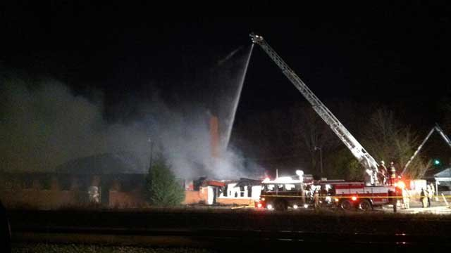Firefighters spray water on the smoldering remains of an abandoned mill destroyed by fire. (March 7, 2013/FOX Carolina)