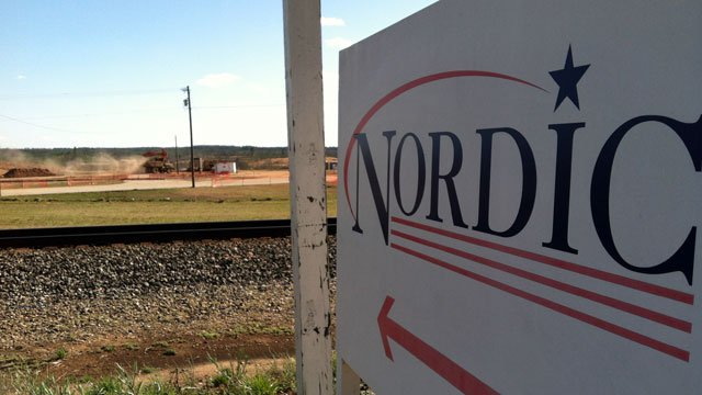 Earth movers operate in the background as a sign points the way to Nordic in Greer. (March 13, 2013/FOX Carolina)