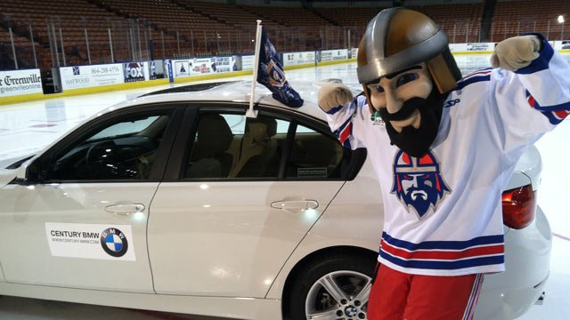 The Road Warriors' mascot Rowdy alongside the BMW that may be given away to a lucky contestant during Friday's game. (Mar. 29, 2013/FOX Carolina)