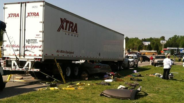 The tractor trailer was lifted up to help remove the driver from within the car. (Apr. 22, 2013/FOX Carolina)