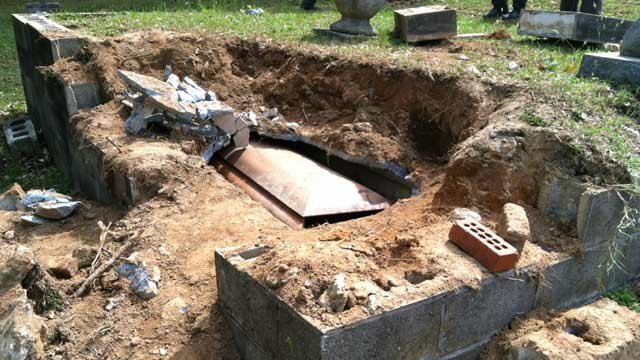 Pieces of concrete and chunks of dirt lay strewn about the grave site after police say someone broke into the coffin. (March 28, 2012/FOX Carolina)