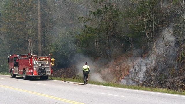 Firefighters work to extinguish a brush fire along U.S. 64 in Transylvania County. (Apr. 26, 2013/FOX Carolina)