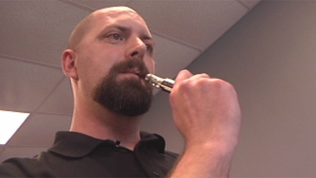 Jason Haggan smokes an electronic cigarette at his shop. (May 6, 2013/FOX Carolina)