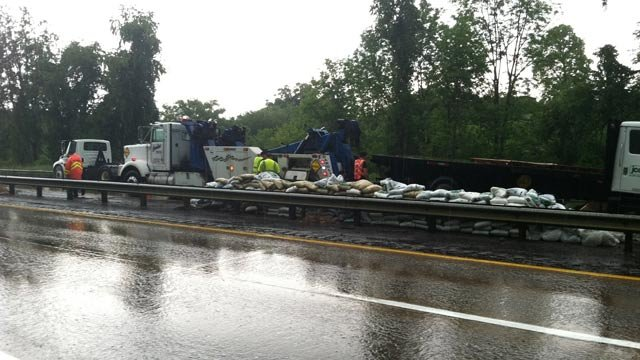 Crews stacked the fertilizer along the guardrail and worked to tow the truck away. (May 22, 2013/FOX Carolina)