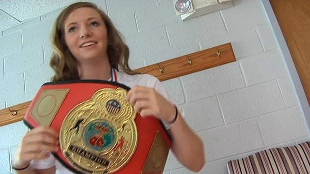 Anna Crutchfield holds up one of her title belts. (July 1, 2013/FOX Carolina)