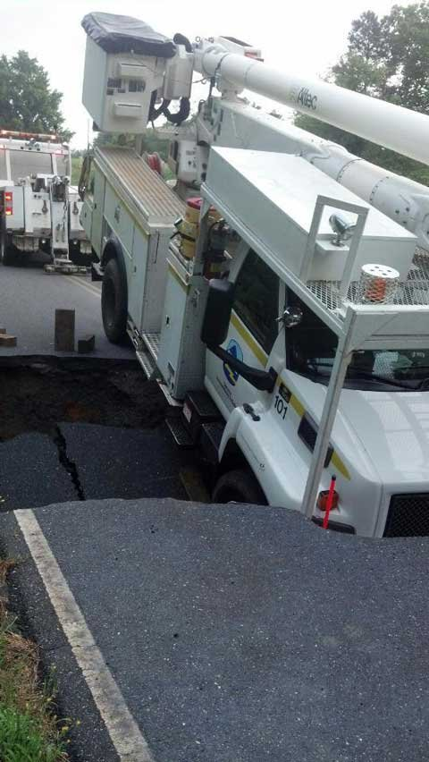 The Blue Ridge Electric bucket truck stuck in the sinkhole. (July 9, 2013/FOX Carolina iWitness Mike F.)
