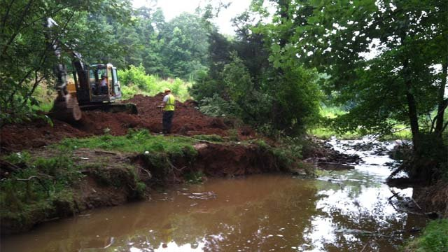Crews work on a sewage spill and broken pipe in Simpsonville along Bridge Fork Creek. (July 10, 2013/FOX Carolina)