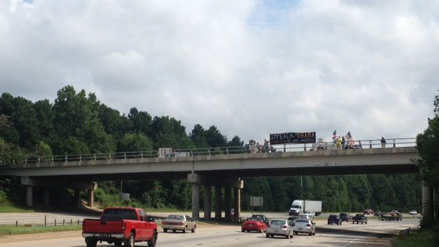 Protesters wave flags and hold signs at an overpass in Spartanburg Co. (8/6/2013 FOX Carolina)
