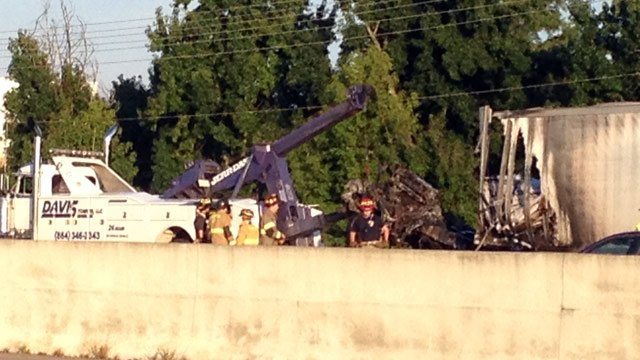 A wrecker works to tow away the burned out tractor-trailer. (Sept. 6, 2013/FOX Carolina)
