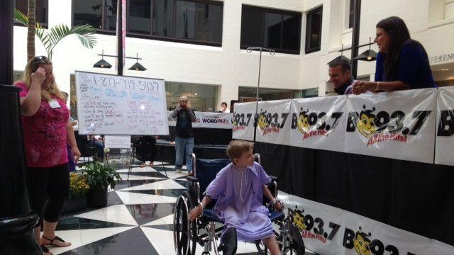 FOX Carolina's Cody Alcorn and B93.7's Heidi Aiken talk to a young fan at the radiothon. (FOX Carolina/Sept. 20, 2013)