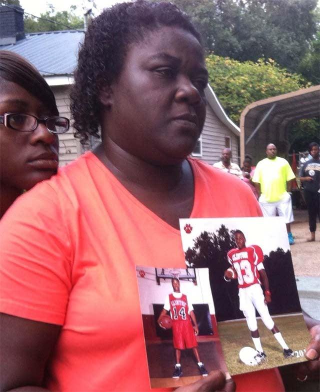 Suzette Byrd holds up photos of her son Eugene Kinard. (Sept. 24, 2013/FOX Carolina)