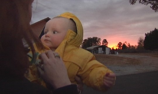 Baby Wyatt and his mom overlook the fire damage. (Nov. 12, 2013/FOX Carolina)