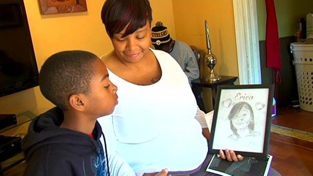 Erica Fields' mother and brother hold a drawing of her. (Nov. 13, 2013/FOX Carolina)