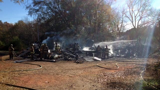 Firefighters investigate the fire at a home on Mountain View Road. (Nov. 19, 2013/FOX Carolina)