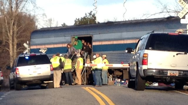 Passengers get off one of the train cars to board charter buses. (Nov. 25, 2013/FOX Carolina)