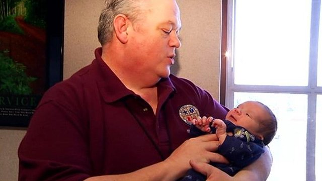 Dispatcher Floyd Thompson holds baby Jude Lutz. (Feb. 5, 2014/FOX Carolina)