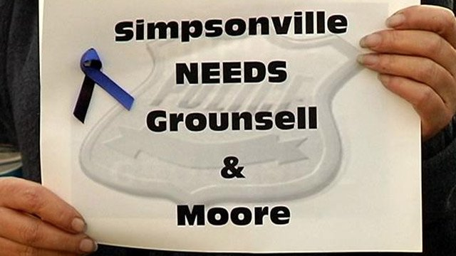 A citizen holds up a sign supporting both Moore and Grounsell at the meeting. (Feb. 25, 2014/FOX Carolina)
