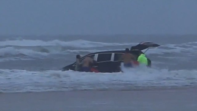 People rush to the van floating into the Atlantic Ocean at Daytona Beach. (Source: Simon Besner)