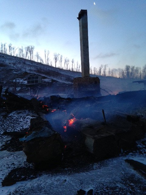 Embers burn in the rubble of the snowy lodge. (March 26, 2014/FOX Carolina)