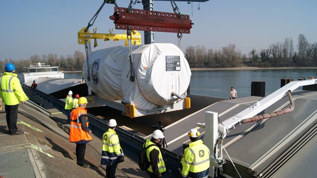 "The 9HA Gas Turbine at Port of Strasbourg, France being transferred from the platform to the barge ""Love Story"" for transportation on the Rhine River to the Port of Antwerp in Belgium. (Source: GE Power & Water)"