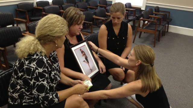 Emily Asbill's mother holds a photo of Emily along with family during the bond hearing in June 2013. (July 2, 2013/FOX Carolina)