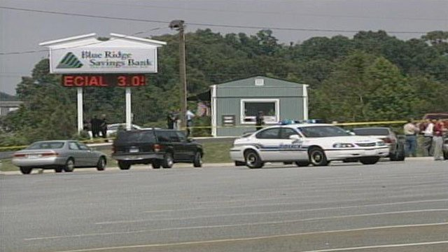 Crime scene tape surrounds Blue Ridge Savings bank in Greer after a triple homicide. (May 16, 2003/FOX Carolina)