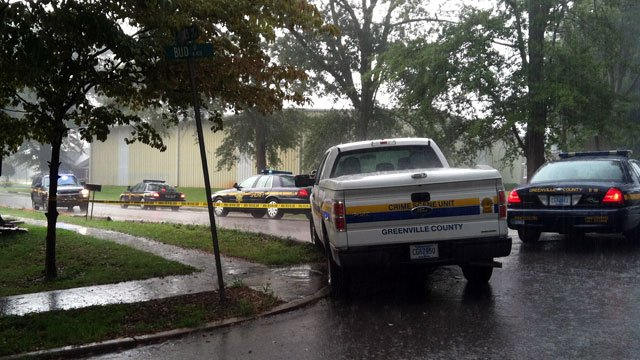 As rain pours, deputies block off a street leading to the scene of a fatal shooting in Berea. (Aug. 21, 2012/FOX Carolina)