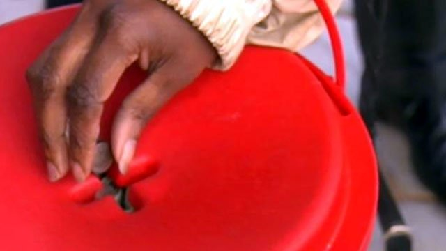 A patron drops some change into a Salvation Army kettle outside an Upstate store.