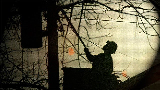 A utility worker repairs a line during an outage. (File/Associated Press)