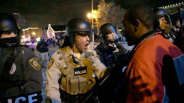 Police officers confront protesters after the announcement of the grand jury decision not to indict police officer Darren Wilson in the fatal shooting of Michael Brown. (AP Photo/David Goldman)