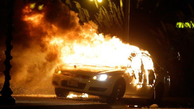 A police car is set on fire after a group of protesters vandalize the vehicle after the announcement of the grand jury decision Monday, Nov. 24, 2014, in Ferguson, Mo. (AP Photo/Charlie Riedel)