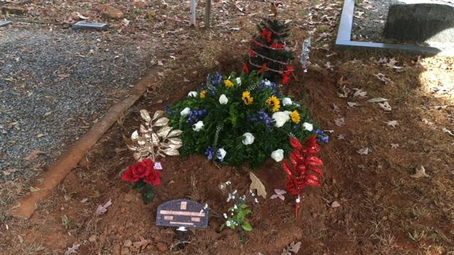 flowers and a new christmas tree are placed at christians grave dec 3