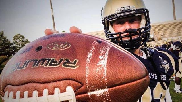 A Spartanburg High School football player holds up a football (File / FOX Carolina)