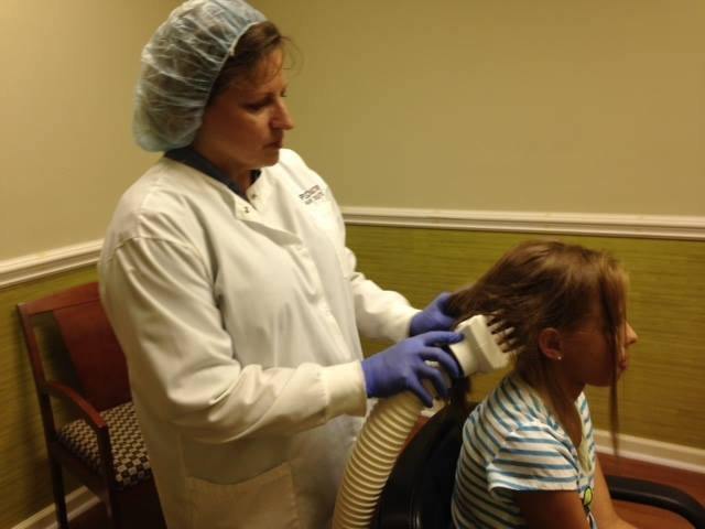 Maureen Rable with Pediatric Hair Solutions demonstrates airflow lice treatment on her daughter (FOX Carolina)